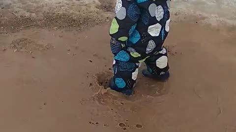 Happy childhood: boy and puddle