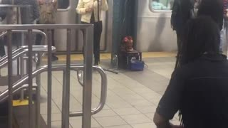 Woman sings man plays drums subway