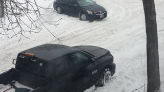 Stuck Car Struggles on Snowy Street