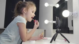 Two Little Girls Putting On Lipstick And Makeup
