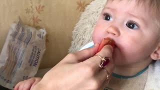 Child eating sour tomato
