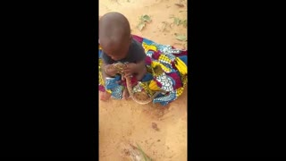 A baby playing with a Snake