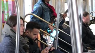 Man sings and plays bass guitar on subway train