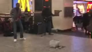 Man plays bass woman in dress dances next to him