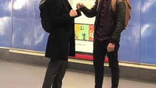 Two men play fight with their arms at subway station