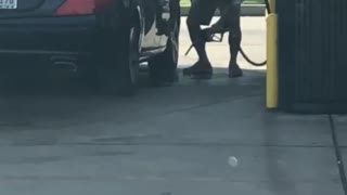 Guy Using Gas at Gas Pump to Clean Car