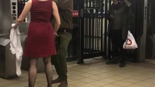 Woman and man dance together next to subway station turnstiles
