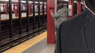 Man uses a blowdryer on his dread inside a subway station