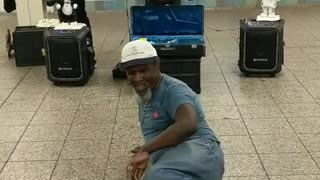 Man in blue shirt jeans dancing subway station