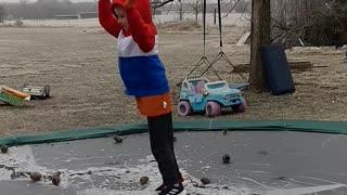 slo motion kid on trampoline falling on ice