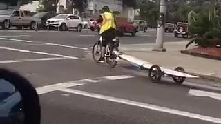 Guy on bike with his surf board behind him