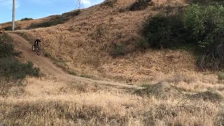 Guy bike goes for small dirt hill jump fails falls into dirt