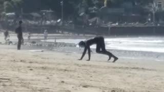 Man in black wetsuit crawling towards beach