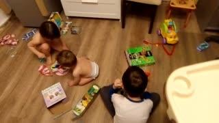 Children open Christmas gifts.