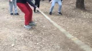 Guys jumping over long tree brach
