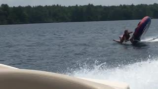 Girl flies off water tube behind boat